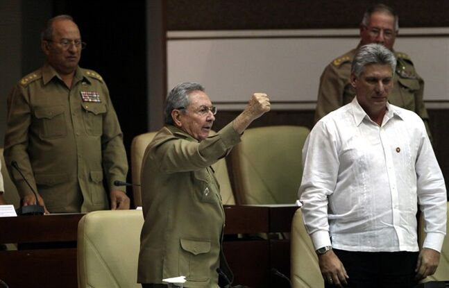 Cuba's President Raul Castro, center left, with a raised fist shouts,