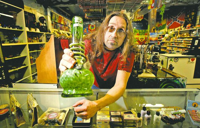 Hemp Haven owner Jeremy Loewen shows off one of the bongs in his Watt Street store last week. He was raided by police last week and hasn't opened since.