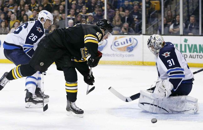 Winnipeg Jets' Ondrej Pavelec (31) deflects a shot by Boston Bruins' Reilly Smith (18) in the second period Saturday.