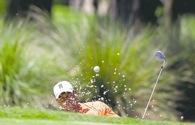 Tiger Woods hits from a bunker on the second hole at TPC Sawgrass on Thursday.