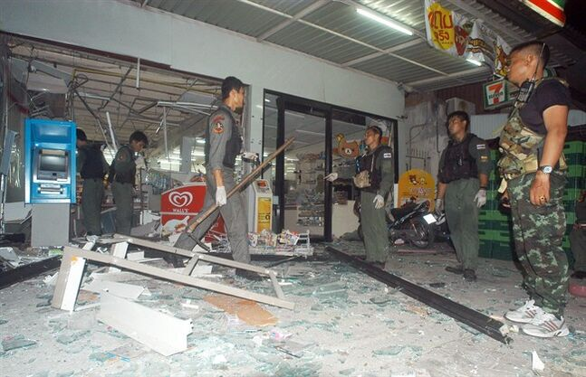 Thai police officers and soldiers examine the site where a bomb exploded at a super store in Pattani province, southern Thailand Saturday, May 24, 2014 Police say at least nine bombs have exploded in Thailand's restive south, killing two people and wounding dozens. The blasts were in a southern province that is facing an Islamic insurgency. (AP Photo/Sumeth Panpetch)