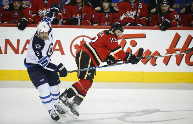 Winnipeg Jets' Mark Stuart, left, knocks Calgary Flames' Lee Stempniak to the ice during the first period.