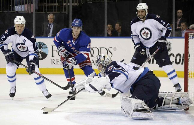 Winnipeg Jets goalie Ondrej Pavelec makes a save as teammates Olli Jokinen (left) and Dustin Byfuglien defends against New York Rangers left-winger Chris Kreider during the second period.