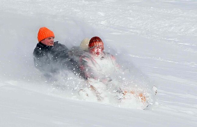 Mark Hachett, right, takes the brunt of the snow as he and his children Kaitlyn, center, and Jacob, left, ride a toboggan at Goodyear Metro Park in Akron, Ohio, on Friday, January 3, 2014.