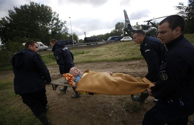 Serbian police officers carry a man from a military helicopter during flood evacuation from Obrenovac, some 30 kilometers (18 miles) southwest of Belgrade Serbia, Saturday, May 17, 2014. Record flooding in the Balkans leaves at least 20 people dead in Serbia and Bosnia and is forcing tens of thousands to flee their homes. Meteorologists say the flooding is the worst since records began 120 years ago. (AP Photo/Darko Vojinovic)