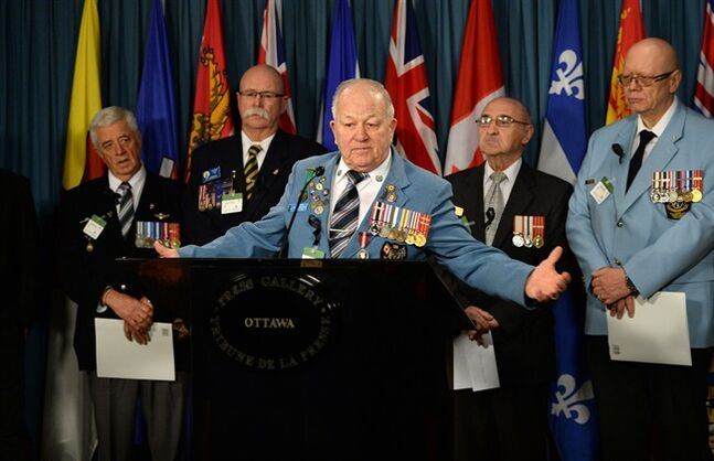 Veteran Ron Clarke joins fellow Veterans and PSAC members as they hold a news conference on Parliament Hill in Ottawa on Tuesday, January 28, 2014. The groups is asking ask the government to reconsider its decision to close Veterans Affairs district offices in nine communities. THE CANADIAN PRESS/Sean Kilpatrick