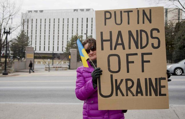 Taisia Bullard, who was born in central Ukraine, holds a protest banner in front in the Russian embassy in Washington, Saturday, March 1, 2014. Russian troops took over Crimea as the parliament in Moscow gave President Vladimir Putin a green light Saturday to use the military to protect Russian interests in Ukraine.
