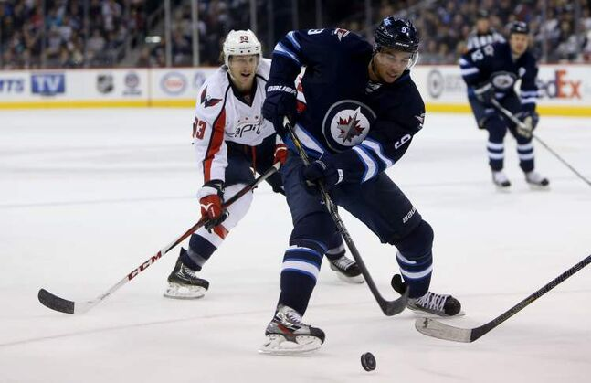Winnipeg Jets' Evander Kane carries the puck in front of Washington Capitals' Jay Beagle late in the second period of Saturday's game.