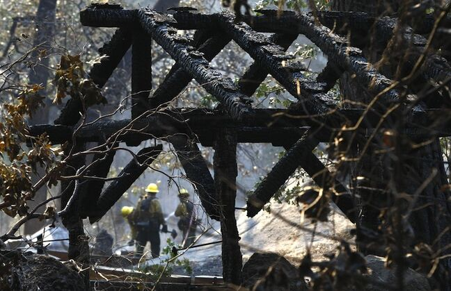 Firefighters douse hot spots amid the smoldering ruins of the Berkeley Tuolumne Camp near Groveland, Calif., Monday. The 1922 village of cabins and a large dining hall on the Tuolumne River that once served 4000 people annually were almost totally destroyed by the massive, uncontrolled Rim fire. All guests had been evacuated. ()
