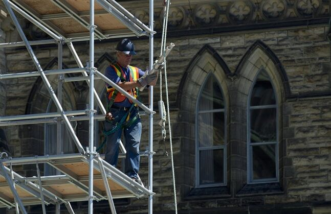 A construction worker holds lifts materials to the second story of centre block on Parliament Hill Friday June 27, 2014 in Ottawa. THE CANADIAN PRESS/Adrian Wyld