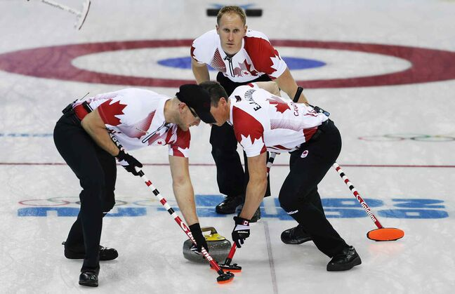 Canada's Brad Jacobs, back, watches as Ryan Harnden, left, and E.J. Harnden, right, sweep during Canada's match against the United States.