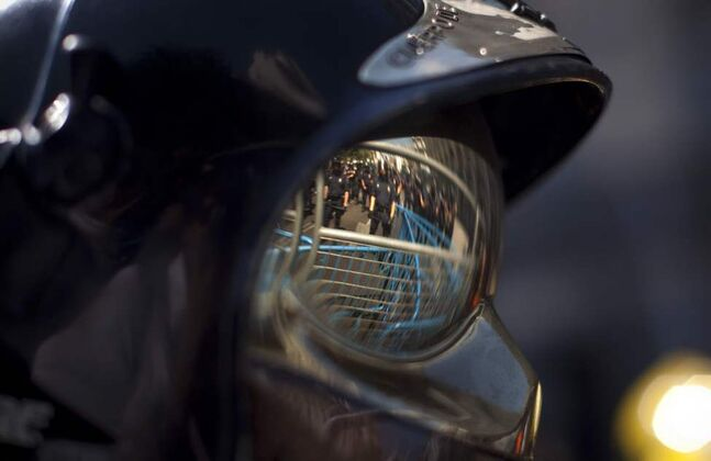 Riot police officers behind barricades are seen reflected on a safety glasses of a protester firefighter as they cordon off the road to block the access of demonstrators during a protest in Madrid, Spain. Firefighters, police in plainclothes and civil servants tried to march on Spain's Parliament to protest stinging austerity measures but were blocked by police in riot gear manning layers of metal fences protecting the legislature. (AP Photo/Emilio Morenatti)