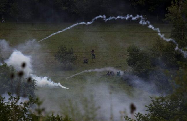 Miners launch handmade rockets to riot police officers, unseen, during clashes following a demonstration after blocking a motorway in Campomanes, Oviedo, Spain, Tuesday, June 12, 2012. Strikes, road blockades, and mine sit-ins continue as 8,000 mineworkers at over 40 coal mines in northern Spain continue their protests against government action to cut coal subsidies.