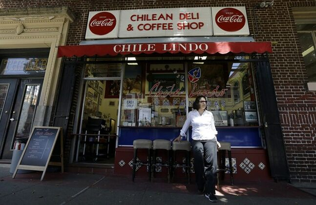 In this June 30, 2014 photo, Paula Tejeda, owner of Chile Lindo, poses for photographs outside of her restaurant in San Francisco. San Francisco and Berkeley are aiming to become the first U.S. cities to pass per-ounce taxes on sugary drinks. (AP Photo/Jeff Chiu)