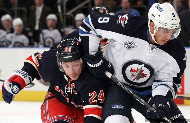 The Jets' Evander Kane controls the puck against the Rangers' Ryan Callahan in their Sunday contest in New York.