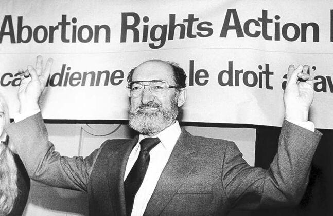 Dr. Henry Morgentaler raises his arms in victory at a news conference in Toronto on Jan. 28, 1988.