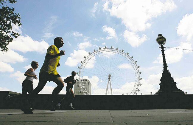 Joggers pass by The London Eye.