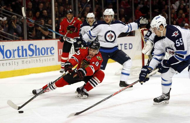 Blackhawks captain Jonathan Toews loses control of the puck in the Jets' end.