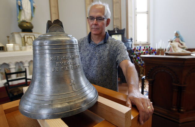 St. Boniface Museum executive director Philippe Mailhot stands with the Bell of Batoche.