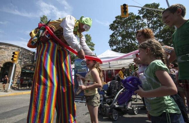 Balloon critters are made to order at the Morden Corn and Apple Festival. Danae Dick, 8, is fitted with a balloon hat while identical twin sister Kaitlyn (right) and others watch.