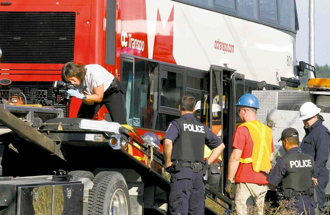 Investigators Thursday examine the site of Wednesday's fatal bus and train crash in Ottawa.