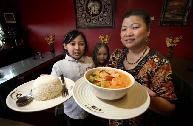 Left to right, Sommerlyn (10), Katana (5) and their grandmother Khamlaa Boonthajit show off a bowl of Gang Pet Curry and a side of rice at Lao-Thai.