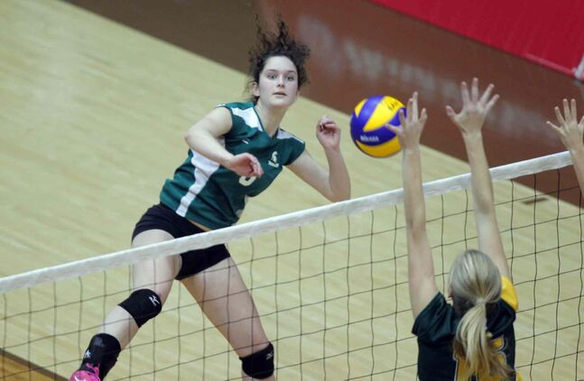 Jordan Hardy (8) of the Neelin Spartans spikes the ball into the hands of Miles Macdonell Buckeyes blockers.