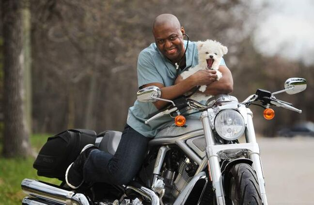 Dr. Donovan Gray sits on his motorcycle with his dog Steth.