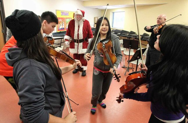 A fiddling class gives an impromptu performance for Santa during his visit to the Black River Anishinabe School on the Little Black River First Nation.