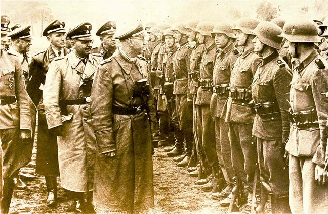 Heinrich Himmler (centre), head of the Gestapo and the Waffen-SS and minister of the interior of Nazi Germany from 1943 to 1945, reviews troops in June 1944.