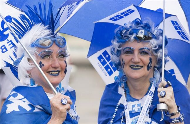 Two colourful members of the crowd enjoy the annual St-Jean-Baptiste Day parade in Montreal, Tuesday, June 24, 2014. THE CANADIAN PRESS/Graham Hughes