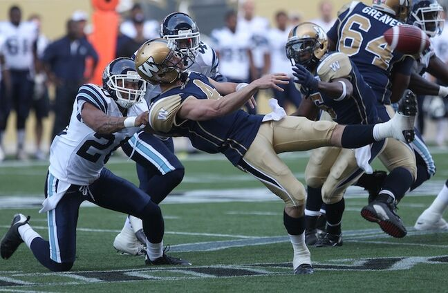 Winnipeg Blue Bombers quarterback Buck Pierce gets sacked by Bryan Payton of the Toronto Argonauts early in the first quarter of their pre-season game at Investors Group Field Wednesday night.