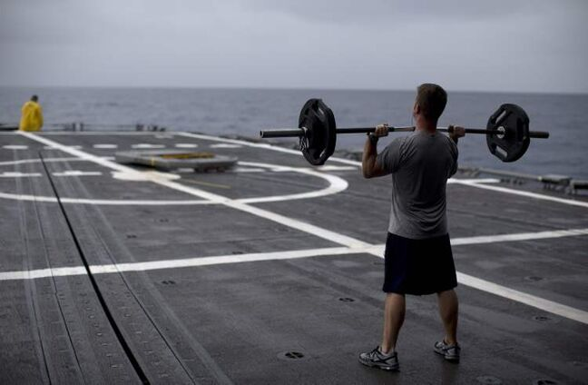 A sailor lifts weights on the flight deck of the the USS Underwood while patrolling in international waters near Panama, Tuesday, Oct. 16, 2012. The USS Underwood is the U.S. Navy's oldest surface combatant ship and is scheduled to be decommissioned in March 2013. 