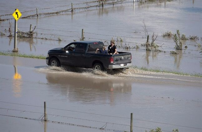 A truck drives down a flooded road on the Siksika First Nation, Alta., on June 23, 2013. THE CANADIAN PRESS/Jonathan Hayward
