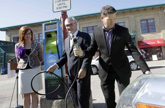From right, Tim Scott of CAA Manitoba prepares to plug in an electric car along with  Municipal Government Minister Stan Struthers, minister responsible for Manitoba Hydro and Clare MacKay with The Forks North Portage Partnership at the unveiling ceremony Thursday morning of the first electric-vehicle charging station, located in the parking lot on the north side of The Forks.