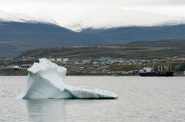 Ice floats past a cargo ship and the hamlet of Pond Inlet on August 24, 2014. THE CANADIAN PRESS/Adrian Wyld