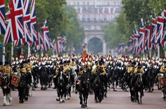 British soldiers ride their horses as the escort Queen Elizabeth II in a horse drawn carriagevas she returns to Buckingham Palace, during the Trooping The Colour parade, in central London, Saturday, June 14, 2014. Hundreds of soldiers in ceremonial dress have marched in London in the annual