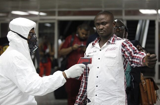 FILE - In this Aug. 6, 2014 file photo, a Nigerian port health official uses a thermometer on a worker at the arrivals hall of Murtala Muhammed International Airport in Lagos, Nigeria. As the Ebola outbreak in West Africa grows, airlines around the globe are closely monitoring the situation but have yet to make any drastic changes. (AP Photo/Sunday Alamba, File)