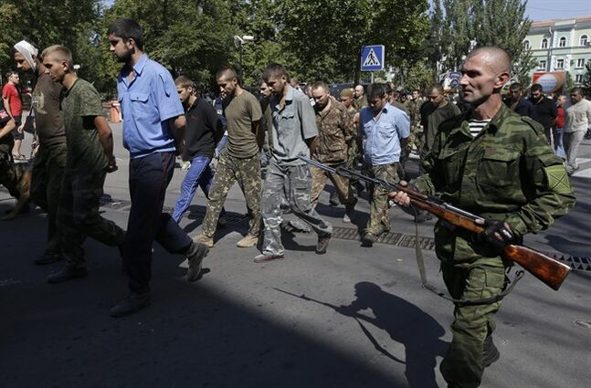Pro-Russian rebels escorting captured Ukrainian army prisoners on central square in Donetsk, eastern Ukraine, Sunday, Aug. 24, 2014. Ukraine has retaken control of much of its eastern territory bordering Russia in the last few weeks, but fierce fighting for the rebel-held cities of Donetsk and Luhansk persists. (AP Photo/Sergei Grits)