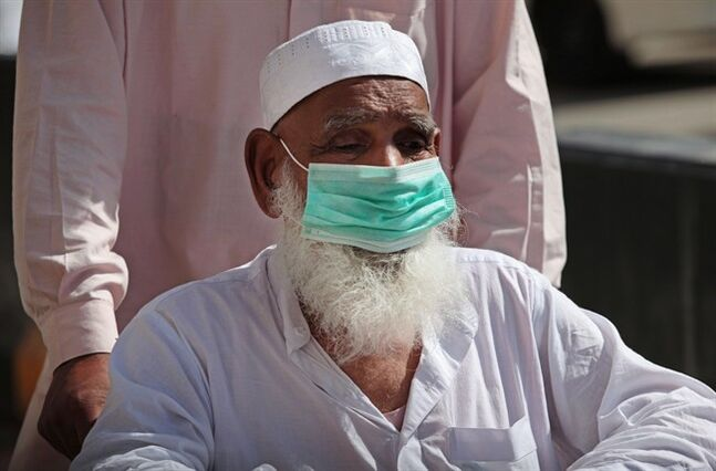 In this photo taken Tuesday, May 13, 2014, a Muslim pilgrim on a wheel chair wears a surgical mask to prevent infection from respiratory virus known as the Middle East respiratory syndrome (MERS) in the holy city of Mecca, Saudi Arabia. THE CANADIAN PRESS/AP, Hasan Jamali