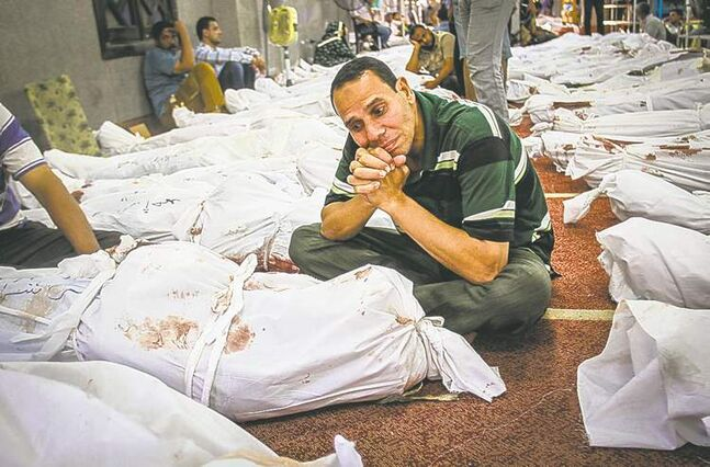 An Egyptian man sits next to the body of a dead relative in the al-Iman mosque amid the bodies of  protesters killed during Wednesday's government crackdown.