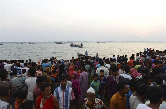 Bangladeshi people gather on the banks of the River Meghna after a ferry carrying more than 100 passengers capsized and sank after being hit by a storm in Munshiganj district, Bangladesh, Thursday, May 15, 2014. According to an official eight bodies have been recovered and there was confusion about the number of missing people. (AP Photo/Sony Ramany)