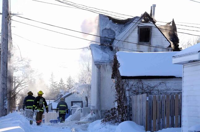 Firefighters battle a blaze at a two-storey home on Chalmers Avenue in Elmwood, Saturday.