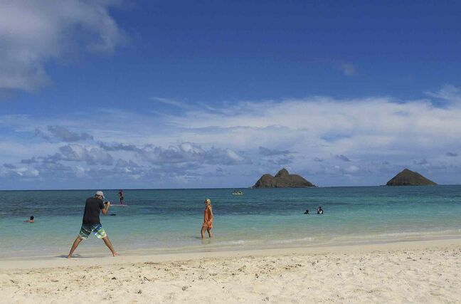 Aloha! Tourists frolic on Lanikai Beach in Kailua, Hawaii.