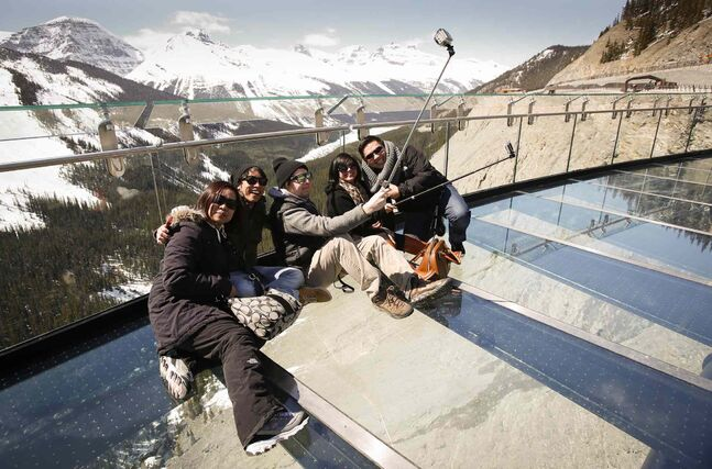 Tourists take selfies with the views from the newly opened Glacier SkyWalk near the Columbia Icefields in Jasper National Park, Alta.
