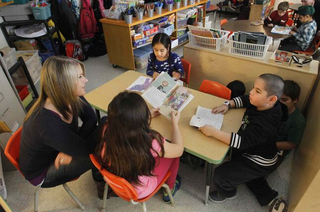 Teacher Erin Murphy works with her grades 2/3 class during reading time at O.V. Jewitt Community School Thursday.