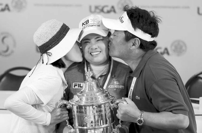 Inbee Park holds her trophy while her parents, Sungja Kim (left) and Gungyu Park, kiss her after she won the U.S. Women's Open on June 30.  Women�s Open golf tournament at Sebonack Golf Club in Southampton, N.Y., Sunday, June 30, 2013. (AP Photo