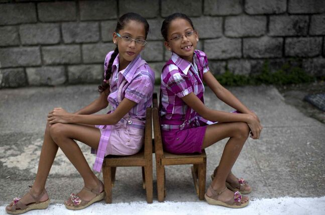 Nine-year-old twin sisters Camila, left, and Carla Rodriguez pose for a portrait along their street in Havana, Cuba.