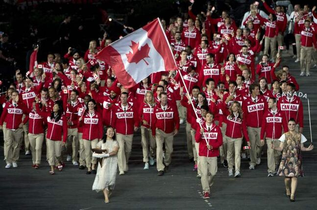 Triathlete Simon Whitfield carries the flag for Team Canada as they enter the stadium during the opening ceremonies for the 2012 Olympic Games in London on Friday.