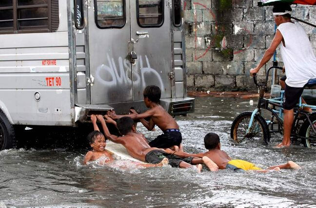 Young boys play in a flooded street,  clinging to the back of a truck Tuesday, July 31, 2012 in Navotas City north of Manila, Philippines.  A typhoon dumped torrents of rain as it swept past the Philippines, killing at least seven people and displacing more than 20,000 others by Tuesday. Another storm lashed the capital and neighboring provinces, leaving several parts of Manila without power and under water.   AP Photo / Pat Roque